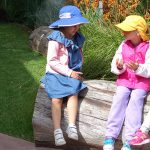 children-sitting-on-a-log-in-garden